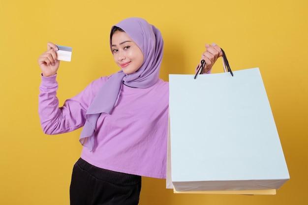Sourire heureuse jolie fille utilisant une carte de crédit pour gaspiller de l'argent dans un centre commercial, tenant des sacs à provisions, acheter des cadeaux ou des cadeaux, offrez-vous la journée