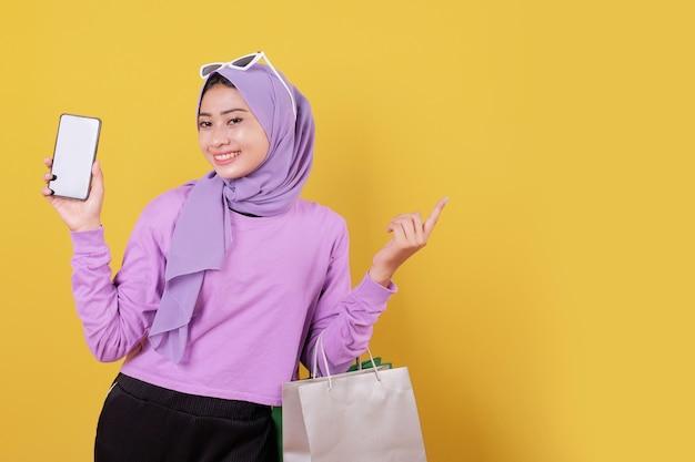 Sourire heureuse jolie fille utilisant une carte de crédit pour gaspiller de l'argent dans un centre commercial, tenant des sacs à provisions, offrez-vous la journée, en riant joyeusement