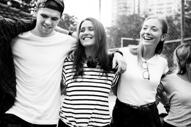 Sourire heureux amis jeunes adultes bras autour de l'épaule à l'extérieur