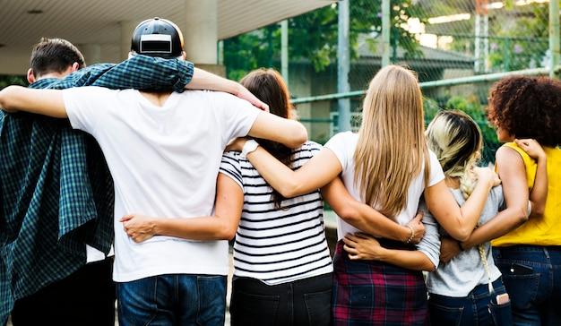 Sourire heureux amis jeunes adultes bras autour de l'épaule en plein air amitié et concept de connexion