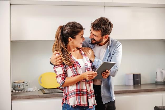 Sourire heureux couple debout ensemble dans la cuisine et à l'aide de tablette pour rechercher une recette.
