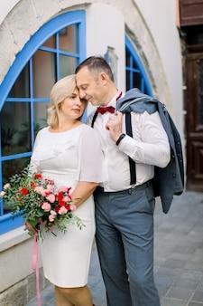Sourire heureux couple marié d'âge mûr amoureux à un rendez-vous dans la vieille ville, debout près les uns des autres lors d'une promenade tranquille en se regardant