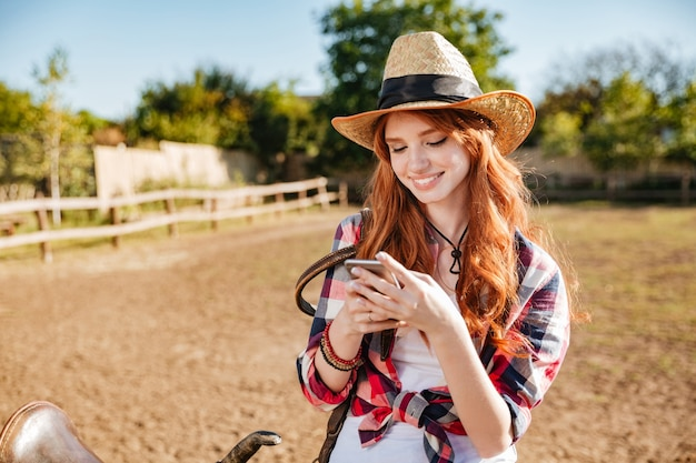 Sourire heureux cowgirl rousse à l'aide de téléphone portable en se tenant debout à la clôture du ranch