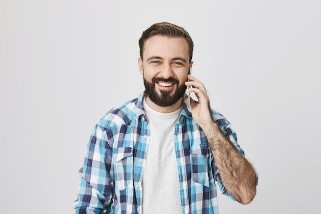 Sourire heureux homme adulte parlant au téléphone