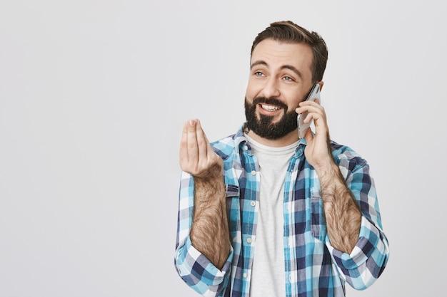 Sourire heureux homme barbu expliquant quelque chose via téléphone mobile, avoir une conversation