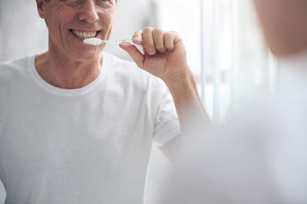 Sourire heureux homme mûr se nettoyant les dents avec une brosse à dents