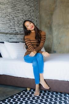 Sourire heureux jeune femme asiatique se détendre sur le lit dans la chambre