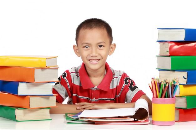 Sourire heureux jeune garçon étudiant autour du livre
