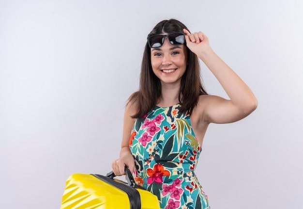 Sourire heureux jeune voyageur femme tenant valise et lunettes de soleil sur mur blanc isolé