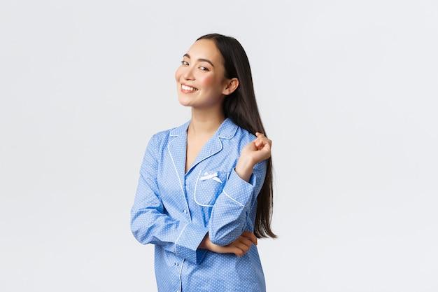 Sourire heureux maquillage de décollage fille asiatique s'apprête à dormir, portant un pyjama bleu et regardant la caméra