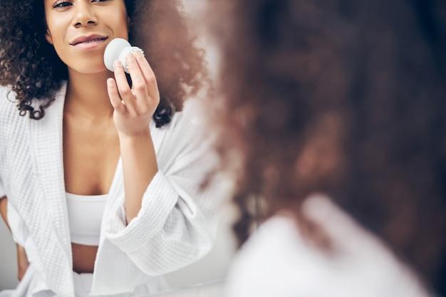 Sourire heureux de nettoyer les pores de la peau de son visage avec une brosse en silicone