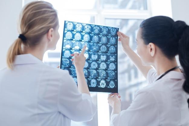 Sourire heureux neurologues qualifiés travaillant au cabinet de roentgen tout en examinant l'image aux rayons x du cerveau et en appréciant la discussion