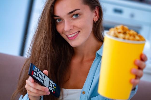 Sourire heureux woman holding crunchy caramel popcorn box et tv remote pendant que vous regardez la télévision à la maison
