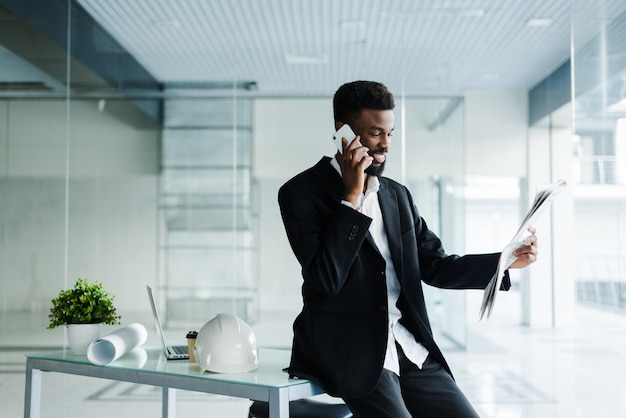 Sourire, homme affaires africain-américain, conversation téléphone, à, journal, et, tasse café, dans, bureau