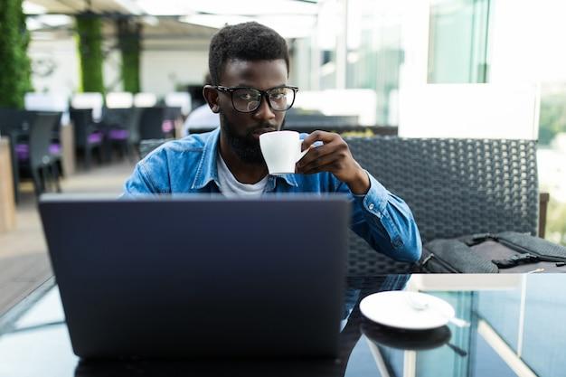 Sourire homme d'affaires africain assis dans un café tenant une tasse de café et utilisant un ordinateur portable.