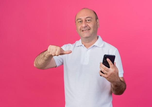 Sourire d'homme d'affaires mature occasionnel tenant et pointant sur un téléphone mobile isolé sur fond rose avec espace de copie