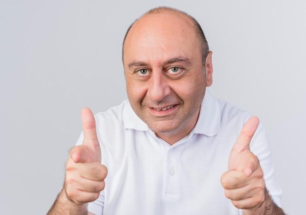 Sourire homme d'affaires mature occasionnel vous faisant un geste à la caméra isolé sur fond blanc