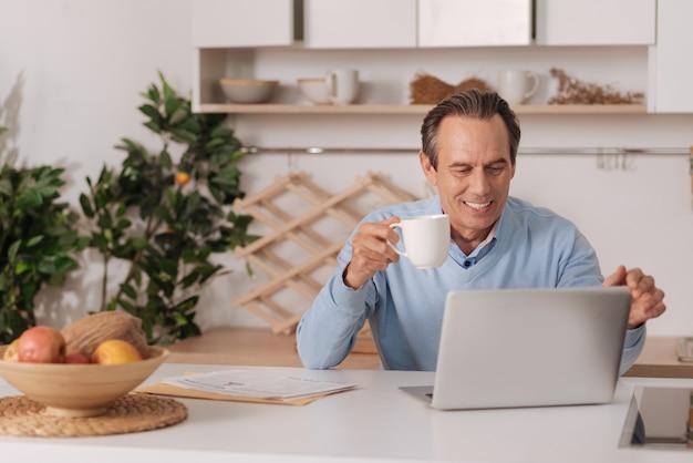 Sourire homme âgé amusé assis dans la cuisine tout en appréciant une tasse de café et en utilisant un ordinateur portable