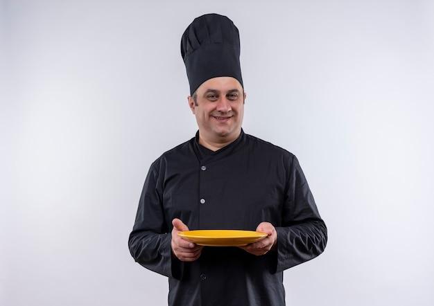 Sourire homme d'âge moyen cuisinier en uniforme de chef tenant la plaque