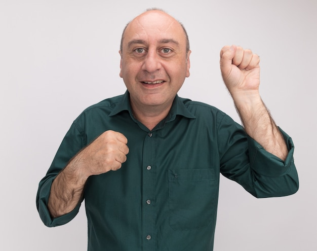 Sourire homme d'âge moyen portant un t-shirt vert debout dans la pose de combat isolé sur mur blanc