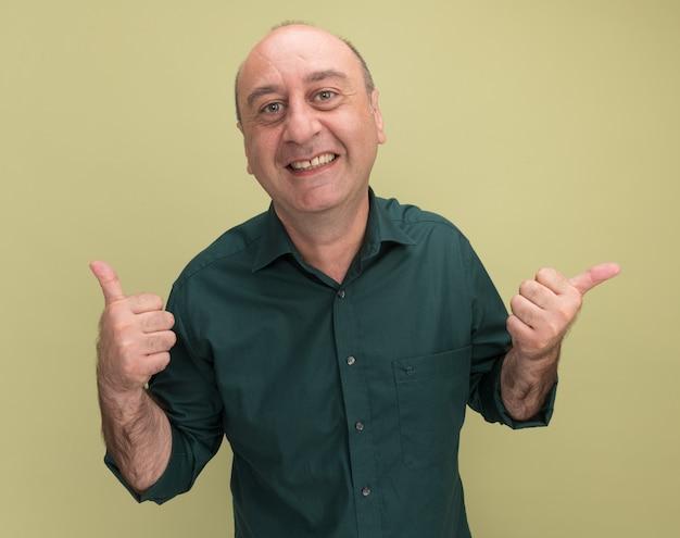 Sourire homme d'âge moyen portant un t-shirt vert montrant le pouce vers le haut et les points sur le côté isolé sur un mur vert olive avec espace copie