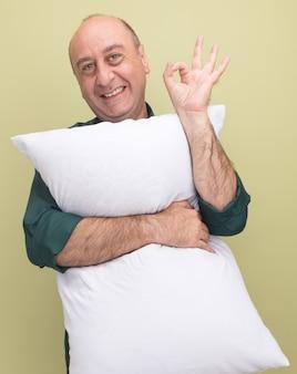 Sourire homme d'âge moyen portant un t-shirt vert oreiller étreint montrant bon geste isolé sur mur vert olive