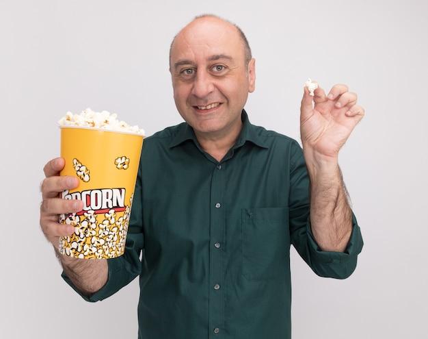 Sourire homme d'âge moyen portant un t-shirt vert tenant un seau de pop-corn avec morceau de pop-corn isolé sur mur blanc