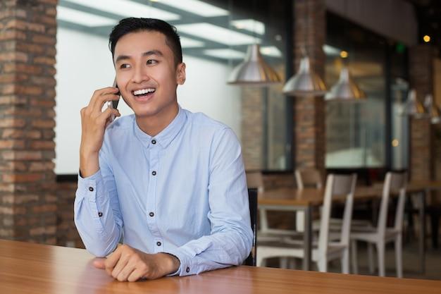 Sourire homme asiatique parlant au téléphone au café table