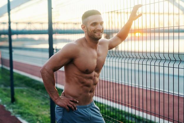 Sourire homme caucasien torse nu appuyé sur une clôture métallique en se tenant debout avec une main sur la hanche sur le court le matin.
