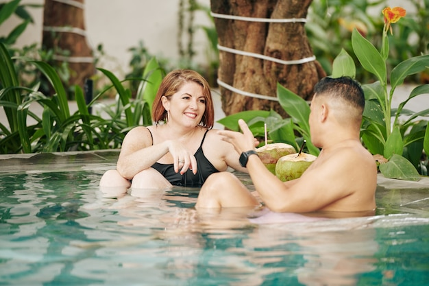 Sourire homme et femme flirter et boire des cocktails à la noix de coco dans la piscine