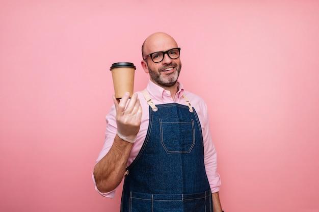 Sourire homme mûr chauve avec du café dans une tasse en carton recyclable