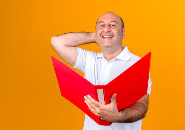 Sourire homme mûr occasionnel tenant le dossier et mettre la main derrière la tête isolé sur jaune