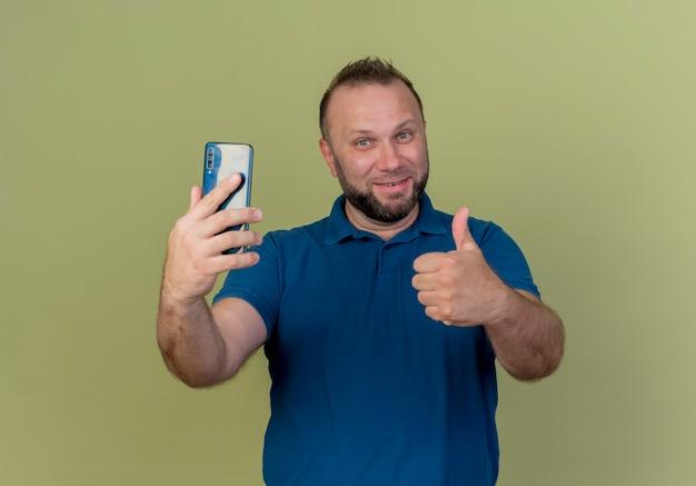 Sourire homme slave adulte tenant un téléphone mobile et montrant le pouce vers le haut