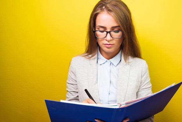 Sourire intelligente femme d'affaires réfléchie avec dossier