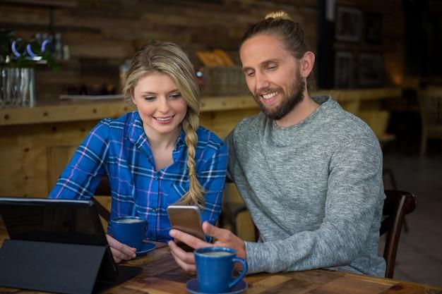 Sourire jeune couple à l'aide de téléphone portable à table au café