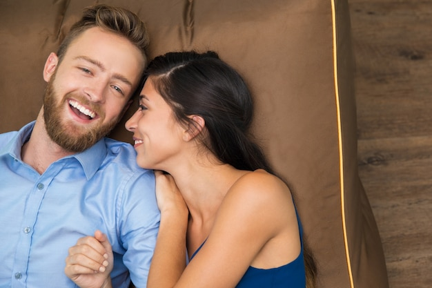 Sourire jeune couple appréciant couché sur le canapé