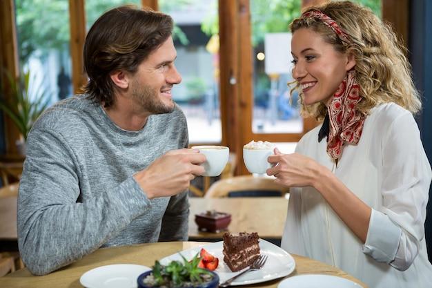 Sourire jeune couple ayant un café à table à la cafétéria