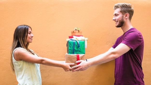 Sourire jeune couple tenant la pile de cadeaux sur fond coloré