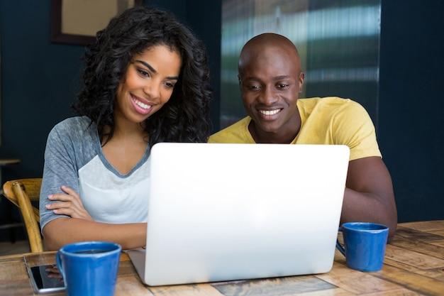 Sourire jeune couple utilisant un ordinateur portable à table dans un café