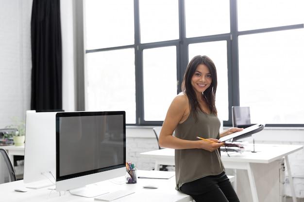Sourire, jeune, femme affaires, tenue, bloc-notes