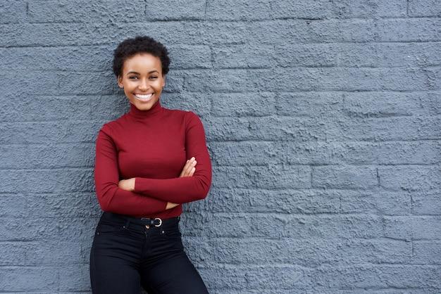 Sourire jeune femme afro-américaine contre le mur gris