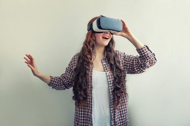 Sourire jeune femme à l'aide de casque de lunettes de réalité virtuelle vr isolé sur blanc