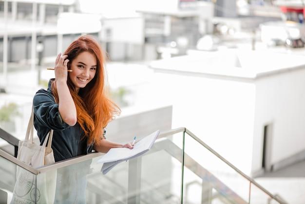Sourire jeune femme ajustant les cheveux sur les escaliers