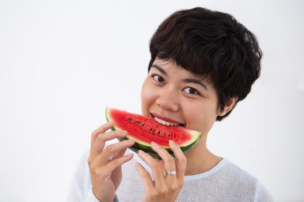 Sourire jeune femme asiatique mordre la pastèque