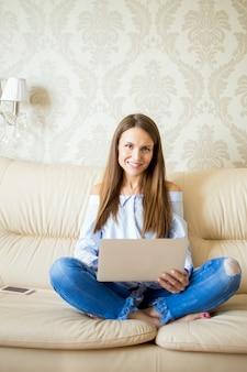 Sourire jeune femme assise sur un canapé avec pavé tactile
