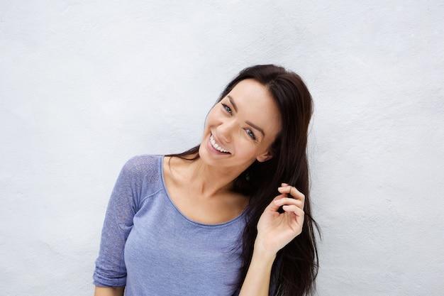 Sourire jeune femme debout contre un mur blanc