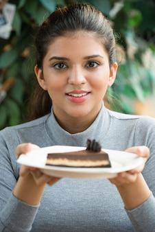 Sourire jeune femme indienne aimant dessert