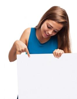 Sourire jeune femme regardant un panneau