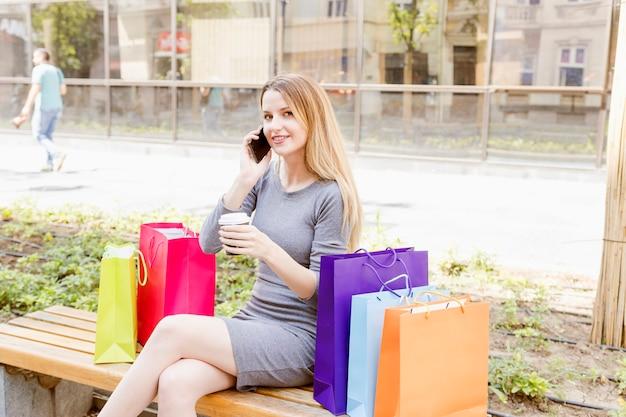 Sourire jeune femme avec des sacs multi couleur parlant sur smartphone dans le parc
