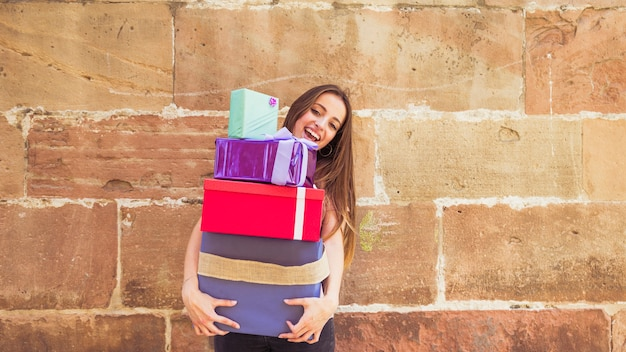 Sourire jeune femme tenant des cadeaux empilés contre le mur altéré